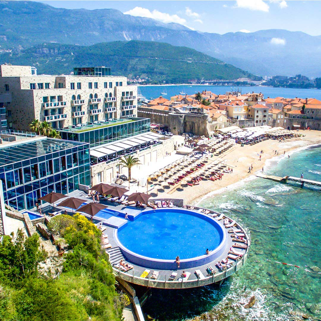 A hotel next to a beach with a pool