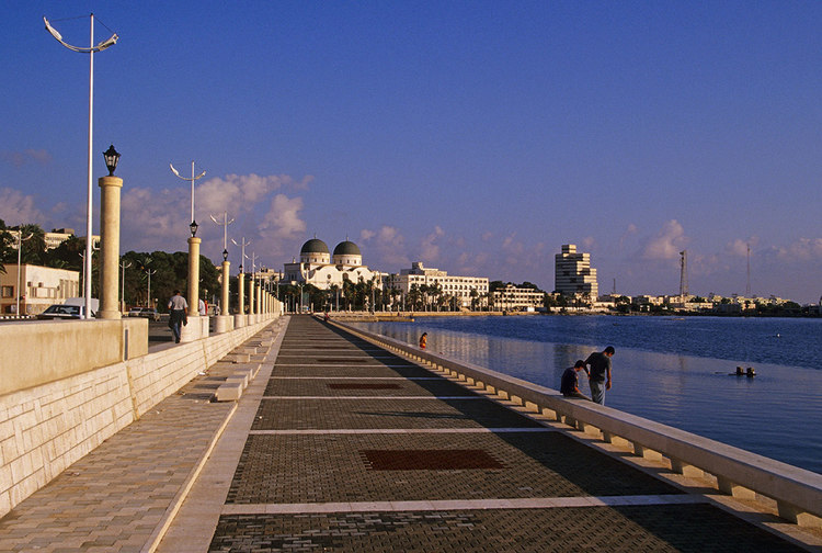People walk along a wide path next to a waterfront