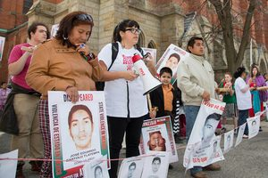 Family members stand holding signs to bring awareness of the Ayotzinapa case
