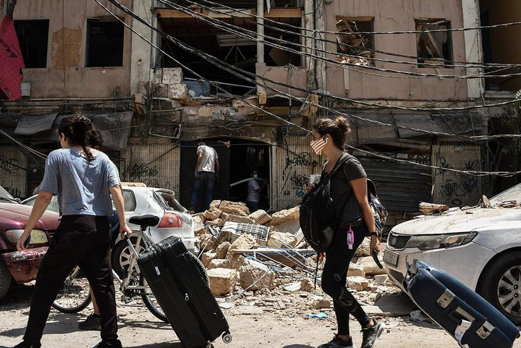 People are seen with suitcases leaving Beirut after the explosion